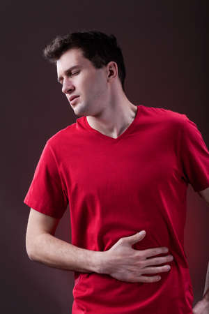 A young man with a stomachache holding his belly