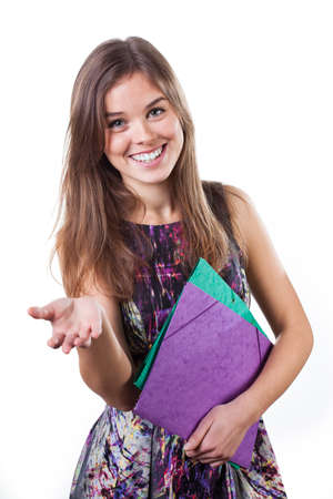 Girl with school folders showing something on the palm of her hand photo