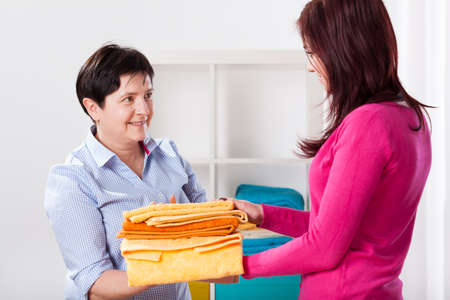 laundry room: Women with pile of folded towels, horizontal