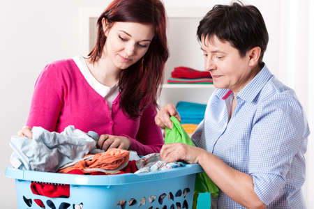Happy women folding laundry at home, horizontal photo