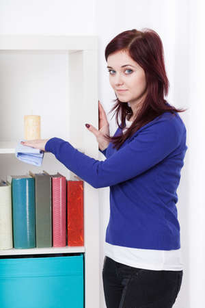 dusting: Young beautiful woman dusting a bookcase, vertical