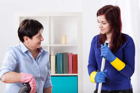 Two women cleaning at house together, horizontal photo
