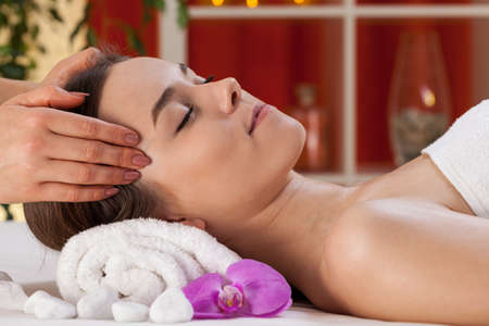 Close-up of relaxed woman receiving head massage photo