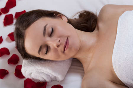 Young woman relaxing at spa with rose petals photo