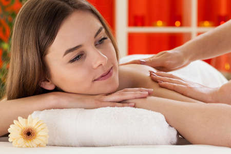 Portrait of a relaxed woman taking massage at spa photo