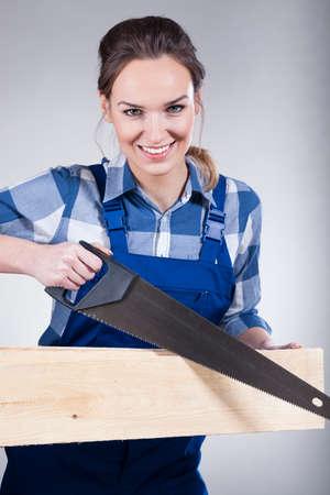 serrucho: Hermosa mujer sonriente con una sierra de mano, vertical Foto de archivo
