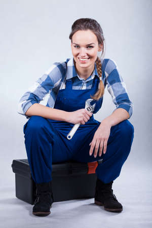 Resting woman sitting on toolbox and holding wrench photo