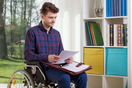 disability insurance: Disabled man on a wheelchair viewing documents