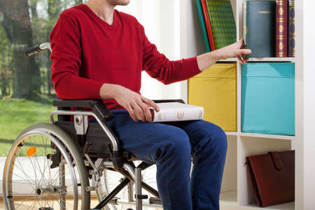 disability insurance: Disabled man on wheelchair clearing out documents