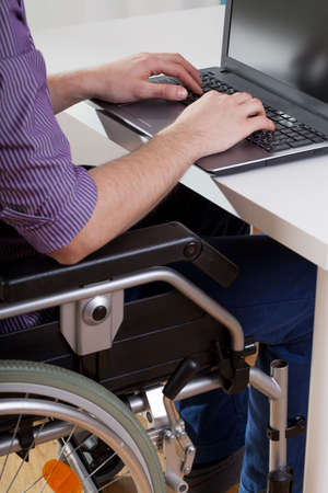disability insurance: Man on wheelchair working on laptop, vertical