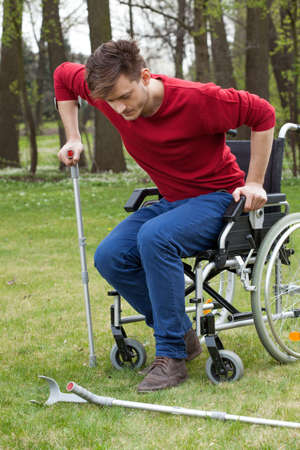 Disabled man on crutches in garden, vertical photo