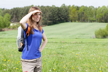something athletic: Girl standing on the meadow and looking at something in the distance Stock Photo