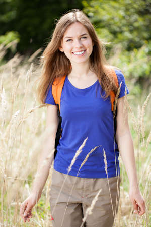 free time: Smiling woman enjoying her time outdoors, vertical