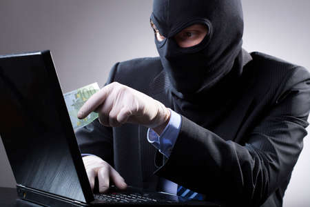 Dangerous businessman uses a laptop with gloves