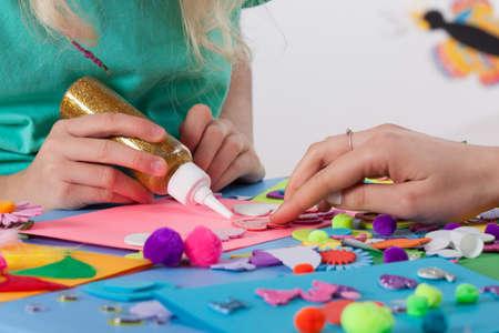 Žena pomáhá dívka na výrobu krásné pohlednice