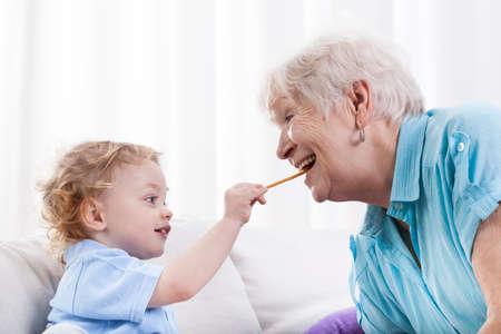 Grandson and his grandma eating together, horizontal photo
