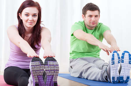 Two young people doing stretching exercises at gym photo