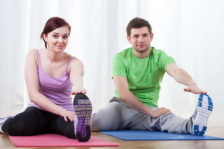 Young couple doing pilates exercises together at gym photo