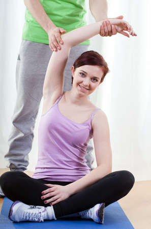 Man assisting young woman in gym exercises photo