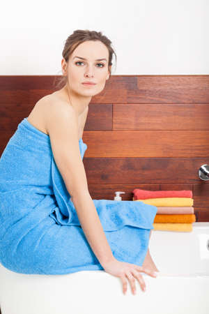 Beautiful young lady in blue towel before bath photo