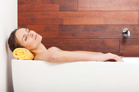 bathroom women: Pretty woman lying in white bath and relaxing Stock Photo