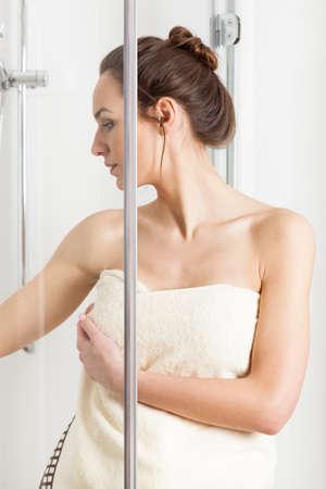 Beautiful woman in white towel finishing a morning shower photo