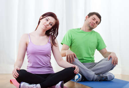Man and woman doing core stretching at gym photo