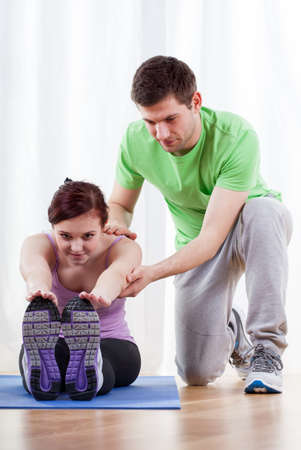 Male trainer helping young woman in exercises photo