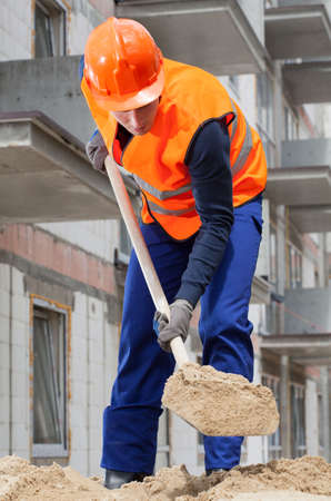 house worker: Builder spanning sand with a spade, vertical