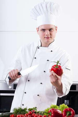 holding a knife: Young fat chef holding a pepper and a knife