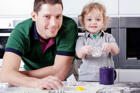 helps: Adorable boy helps his dad bake cupcakes
