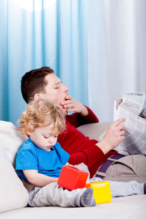 Bored dad reads the newspaper in the room photo