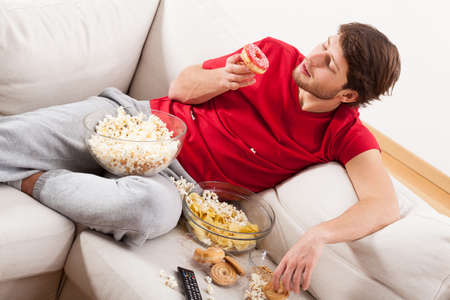 junky: A man lying on a couch with sweets and popcorn in a mess Stock Photo