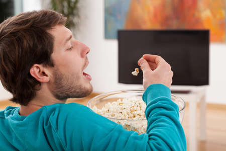 snacking: A man snacking popcorn when watching tv