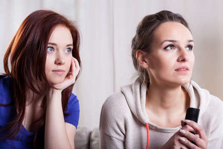 Close-up of two scared women watching television photo