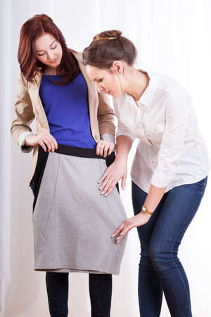pencil skirt: Two female friends trying on pencil skirt, vertical Stock Photo