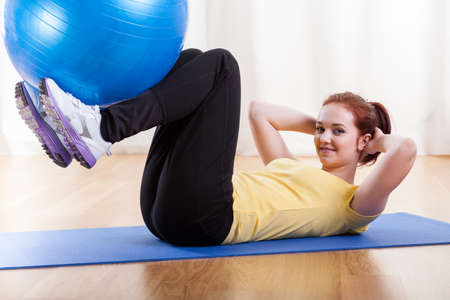 gymnastics equipment: Side view of a girl exercising with gym ball