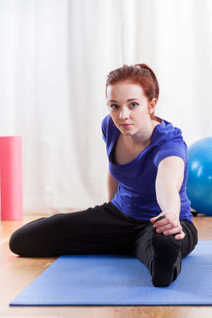 hamstring: Portrait of a girl doing the hamstring stretch on exercise mat