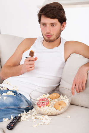 A lazy man sitting on a couch with popcorn and cookies photo