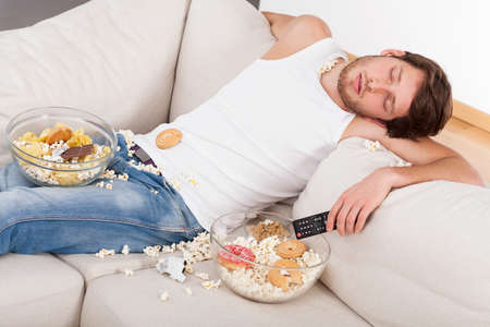 A man sleeping on a couch in a mess of junk food Stock Photo