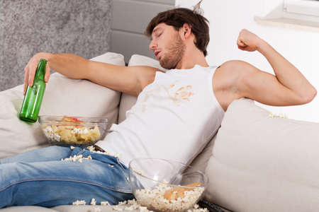A drunk man lying on a couch with popcorn all over the place Stock Photo