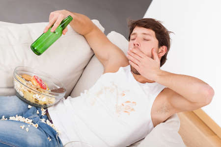 chilling: A tired man yawning on a couch with a bottle and a mess