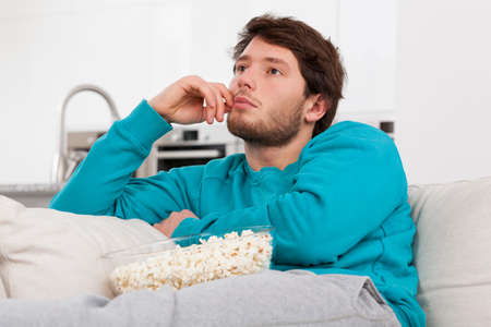 unhealthy living: A man relaxing on a couch with popcorn in comfy clothes