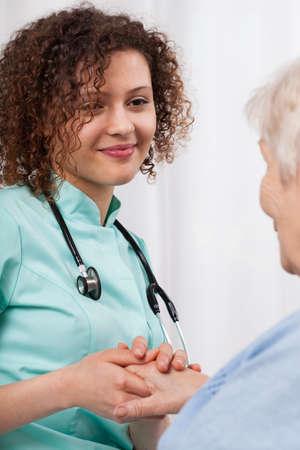 Joven enfermera sosteniendo la mano de una mujer mayor y sonriente Foto de archivo