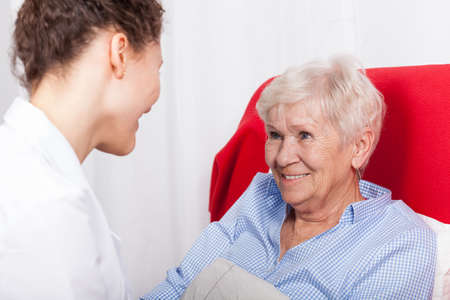Elderly woman sits and smiles to nurses