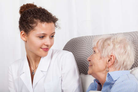 Mature lady and a nurse smiling together photo