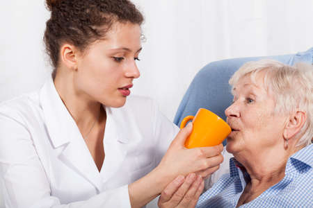 giving hand: Nurse gives something to drink old woman Stock Photo