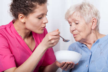 De professionele verpleegkundige het voeden van een oudere dame