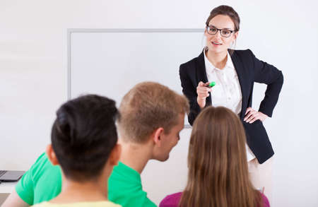 Young teacher pointing on a talking student photo