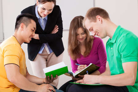 asian teacher: Students working together in the classroom, horizontal